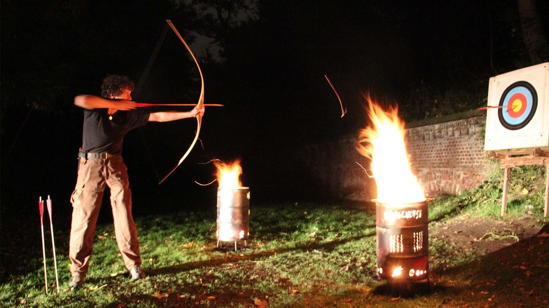 Bogenschütze schießt bei Nacht im Licht von Feuertonnen